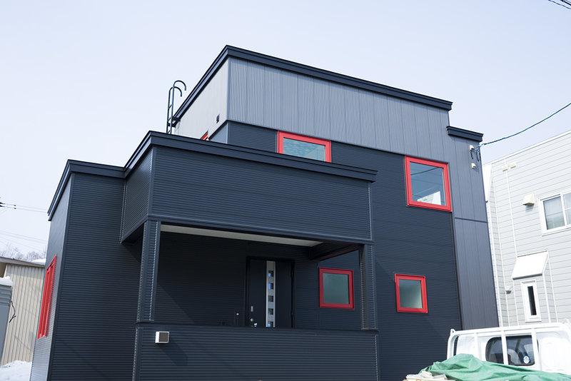グレーのガルバリューム外壁に、赤い窓がアクセント